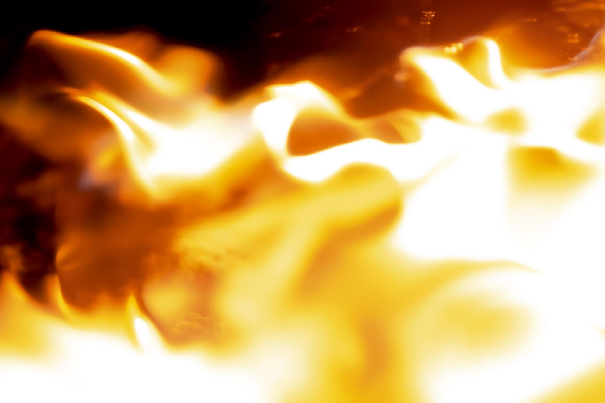 「闇に這うように迫る火炎」