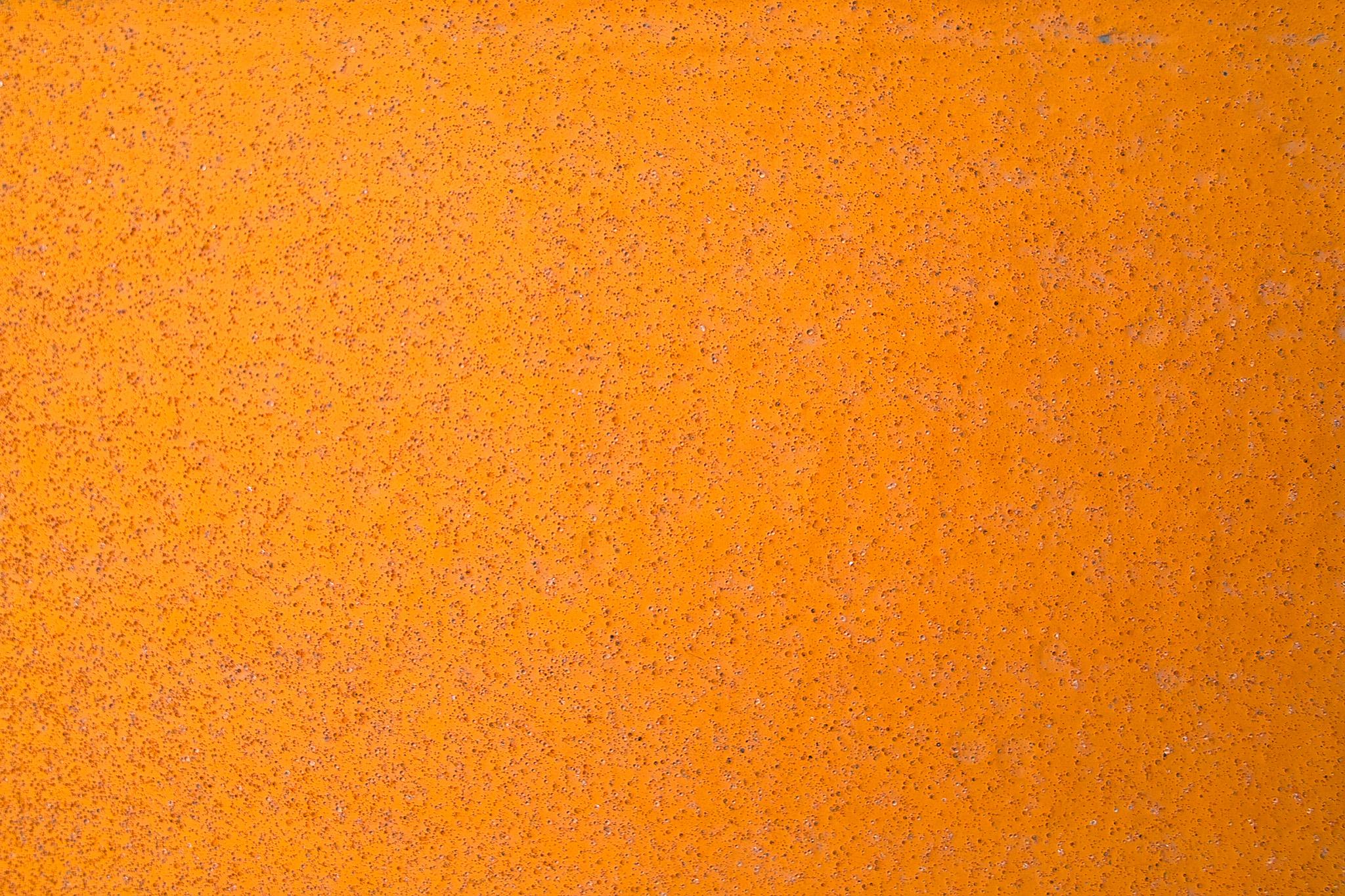 「オレンジ色に塗装された鉄板に細かい錆が浮き出る」