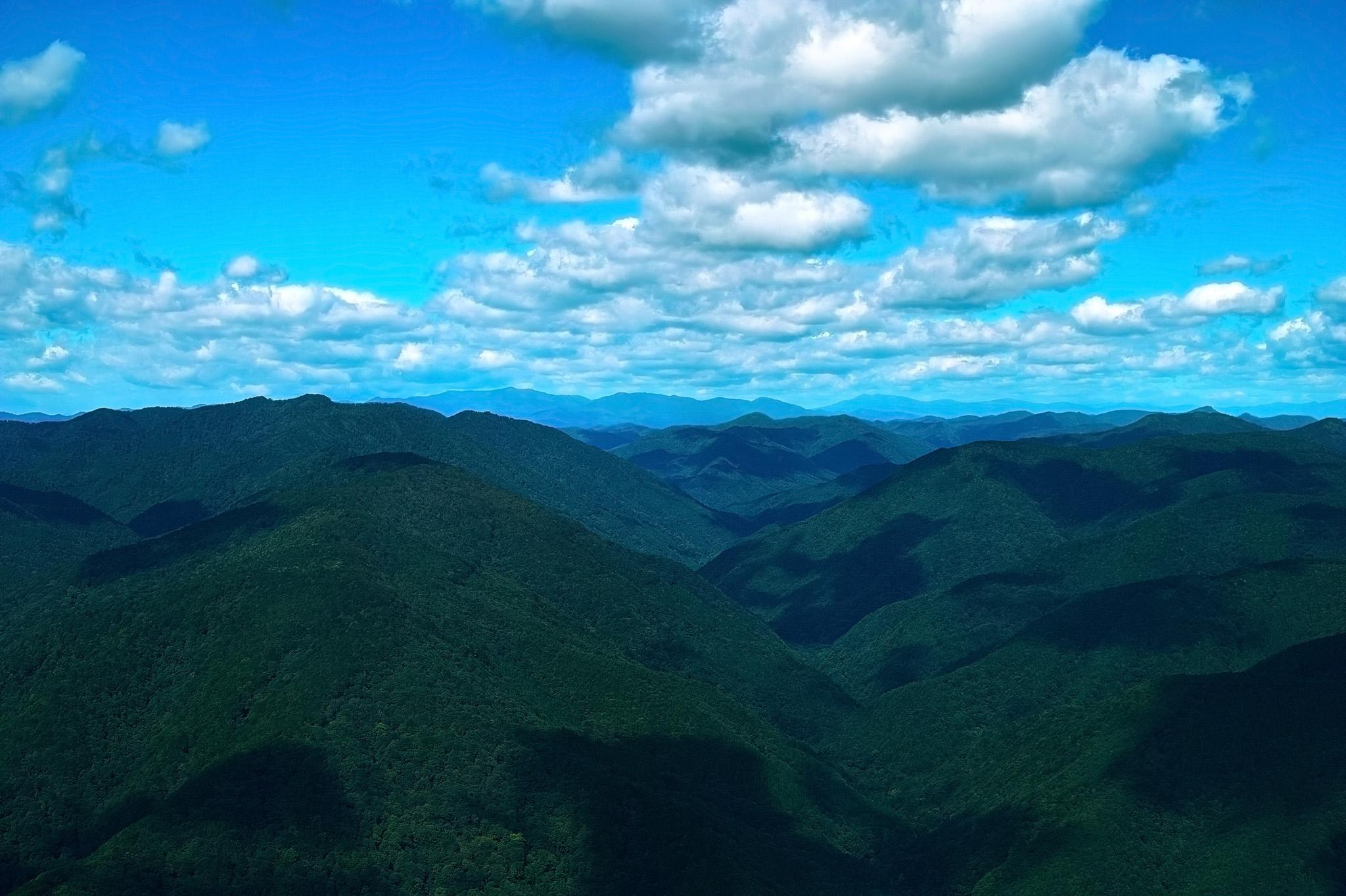 木々が生い茂る山脈に疎らに落ちる雲の影