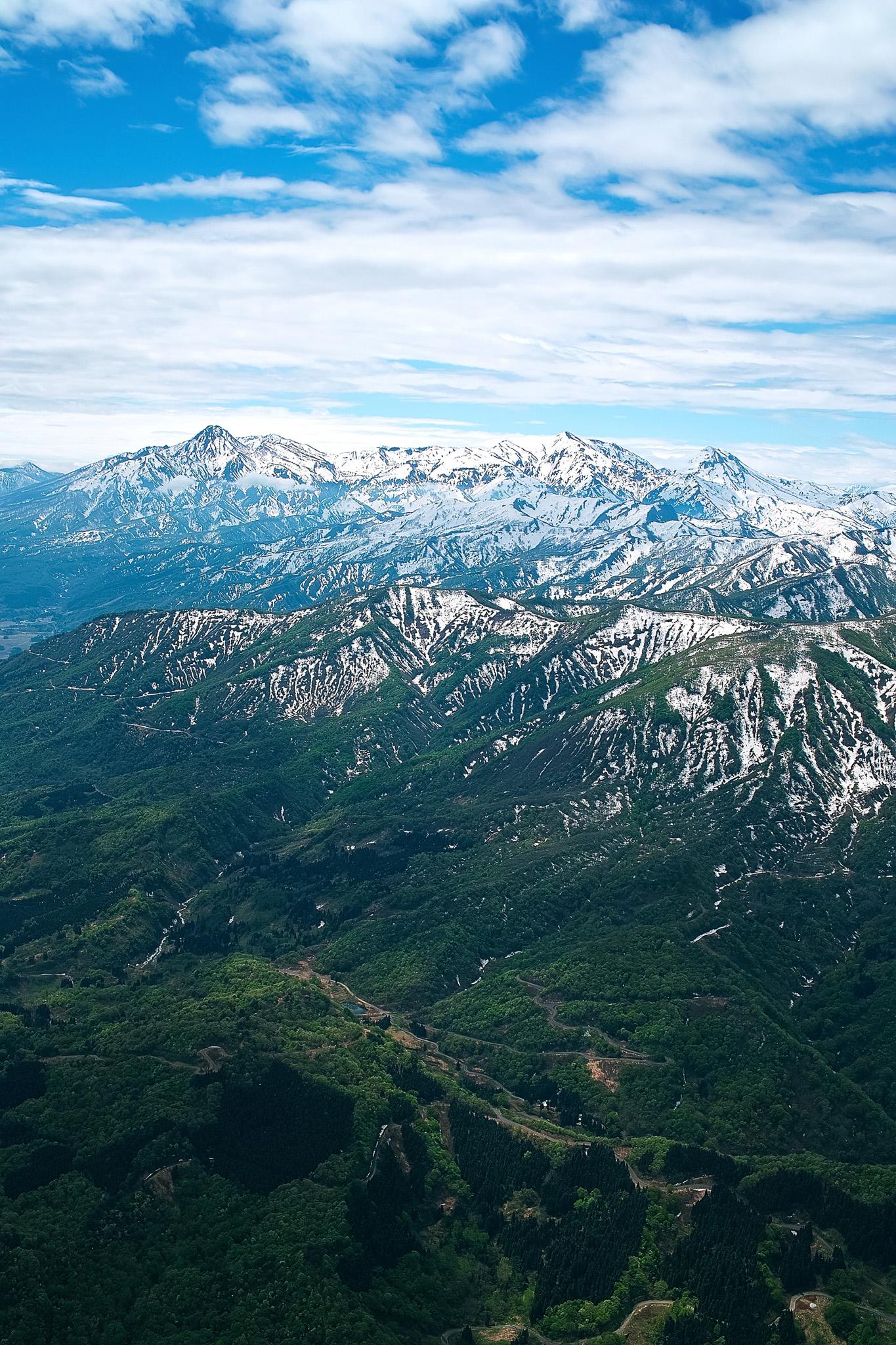 「緑の山麓に残雪の山頂が雄大な春の山地」