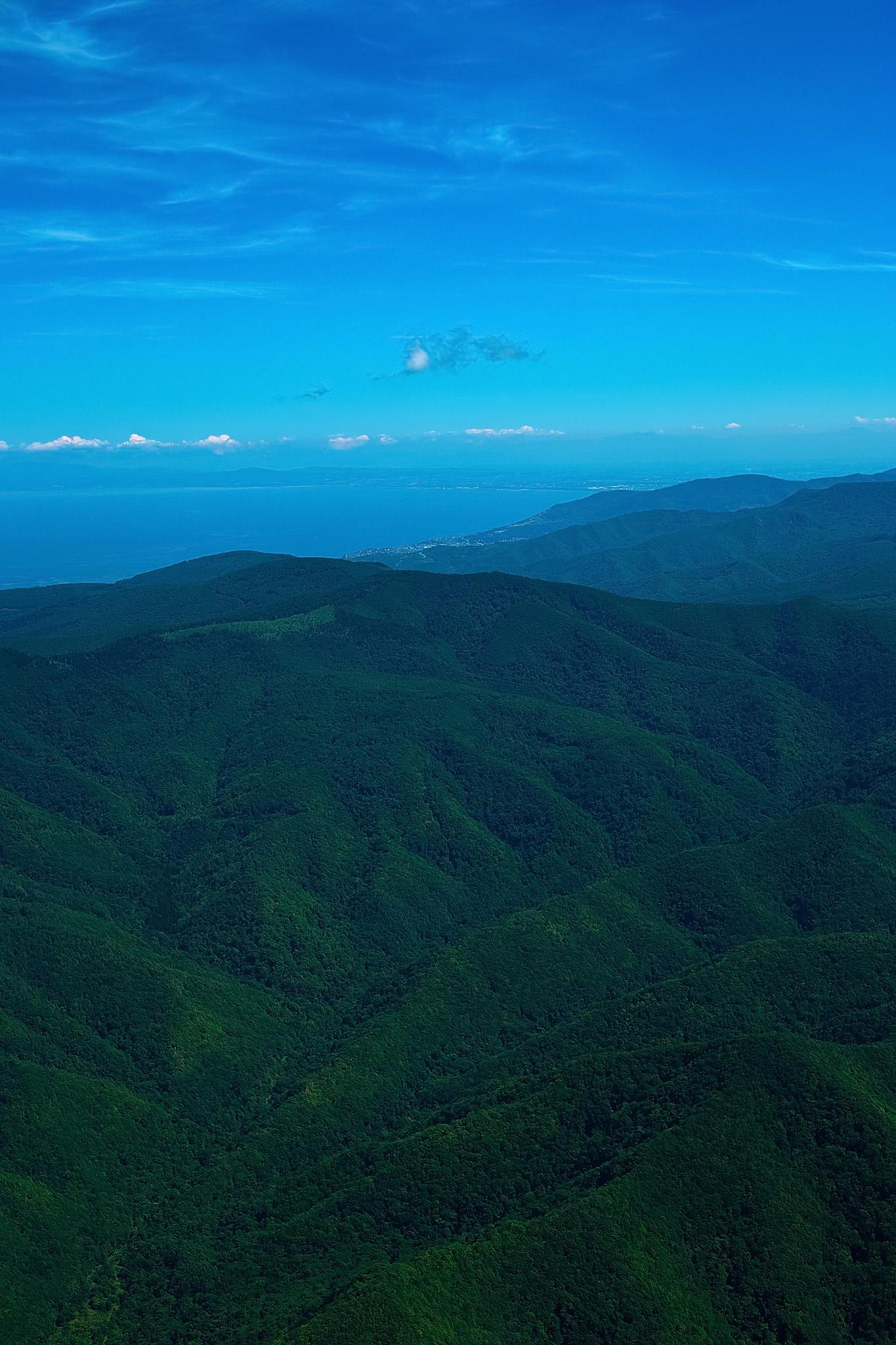 「遠くに海が見える緑濃い山岳」の素材を無料ダウンロード