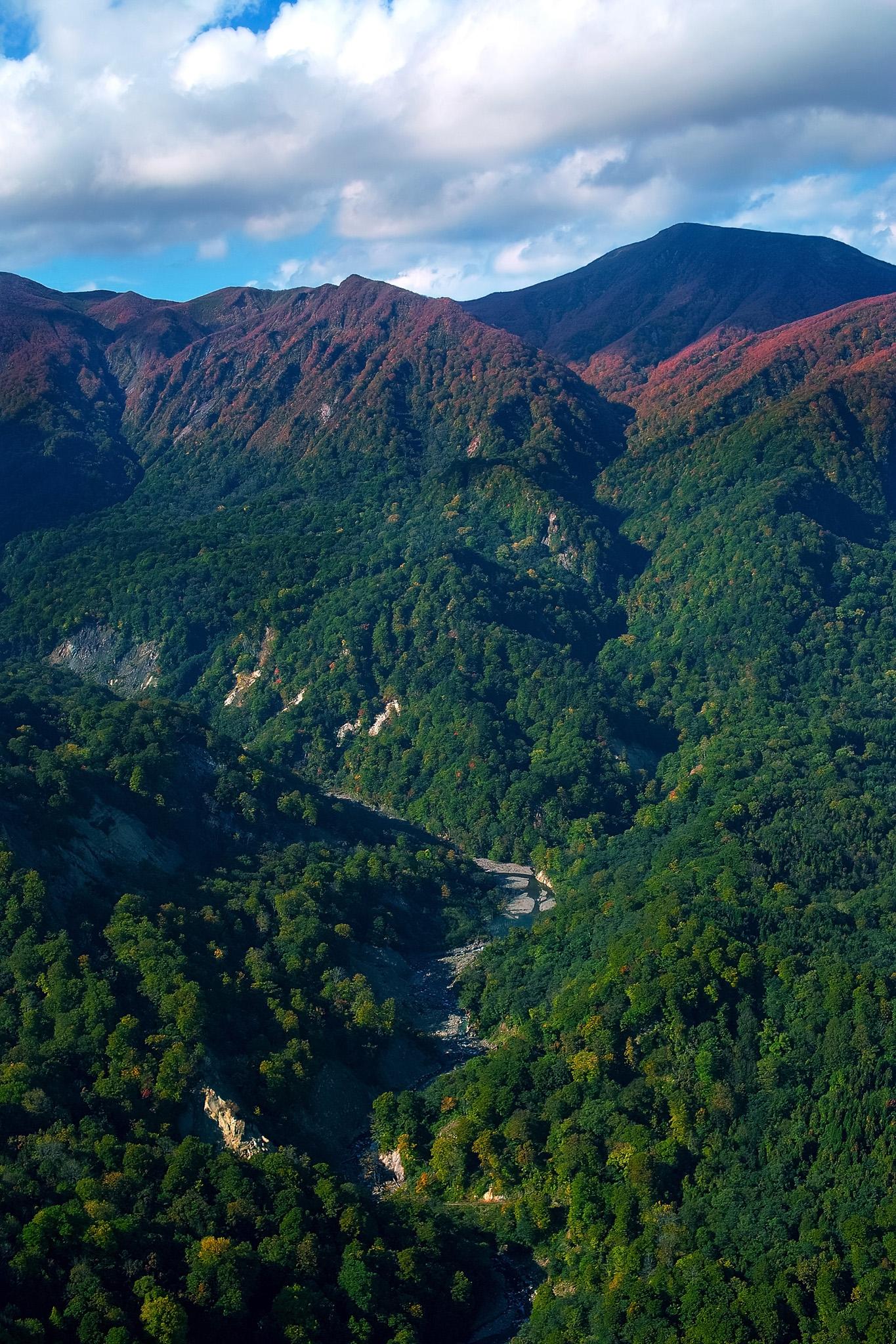 「赤い山頂と緑の麓を流れる渓谷」