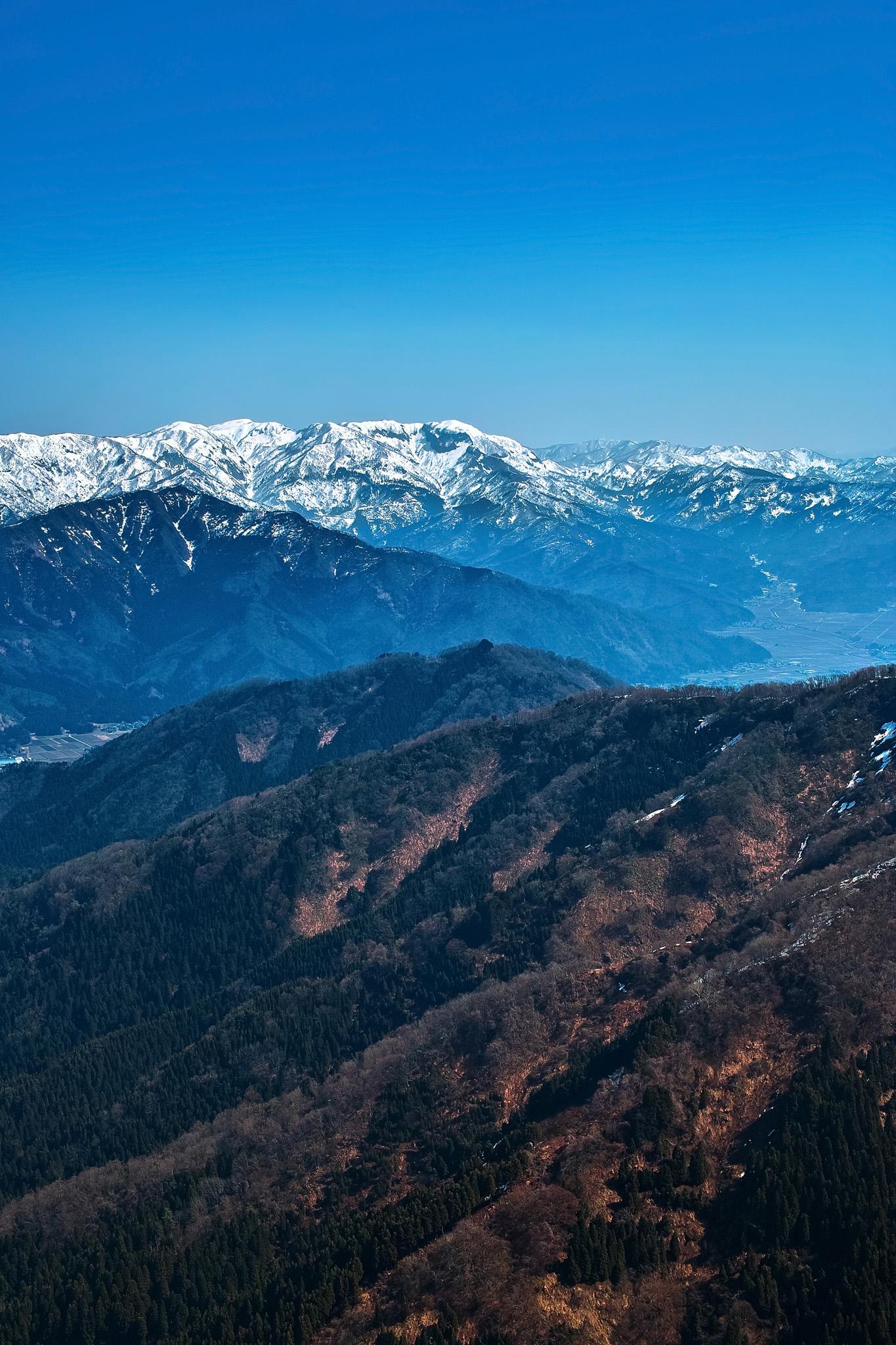 「雪解けした山と雪残る山脈」の画像を無料ダウンロード