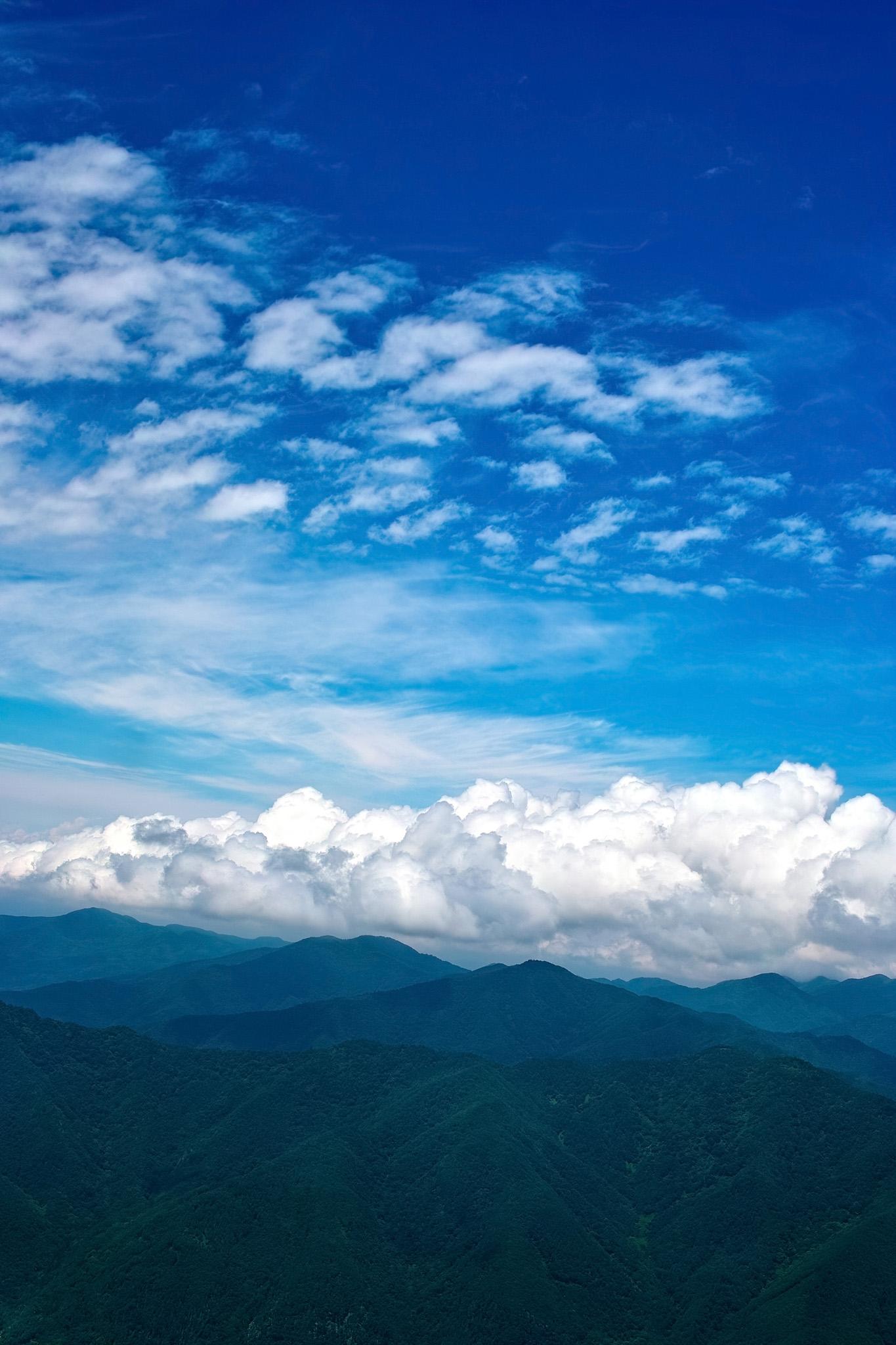「夏空の下に広がる新緑の山々」の画像を無料ダウンロード