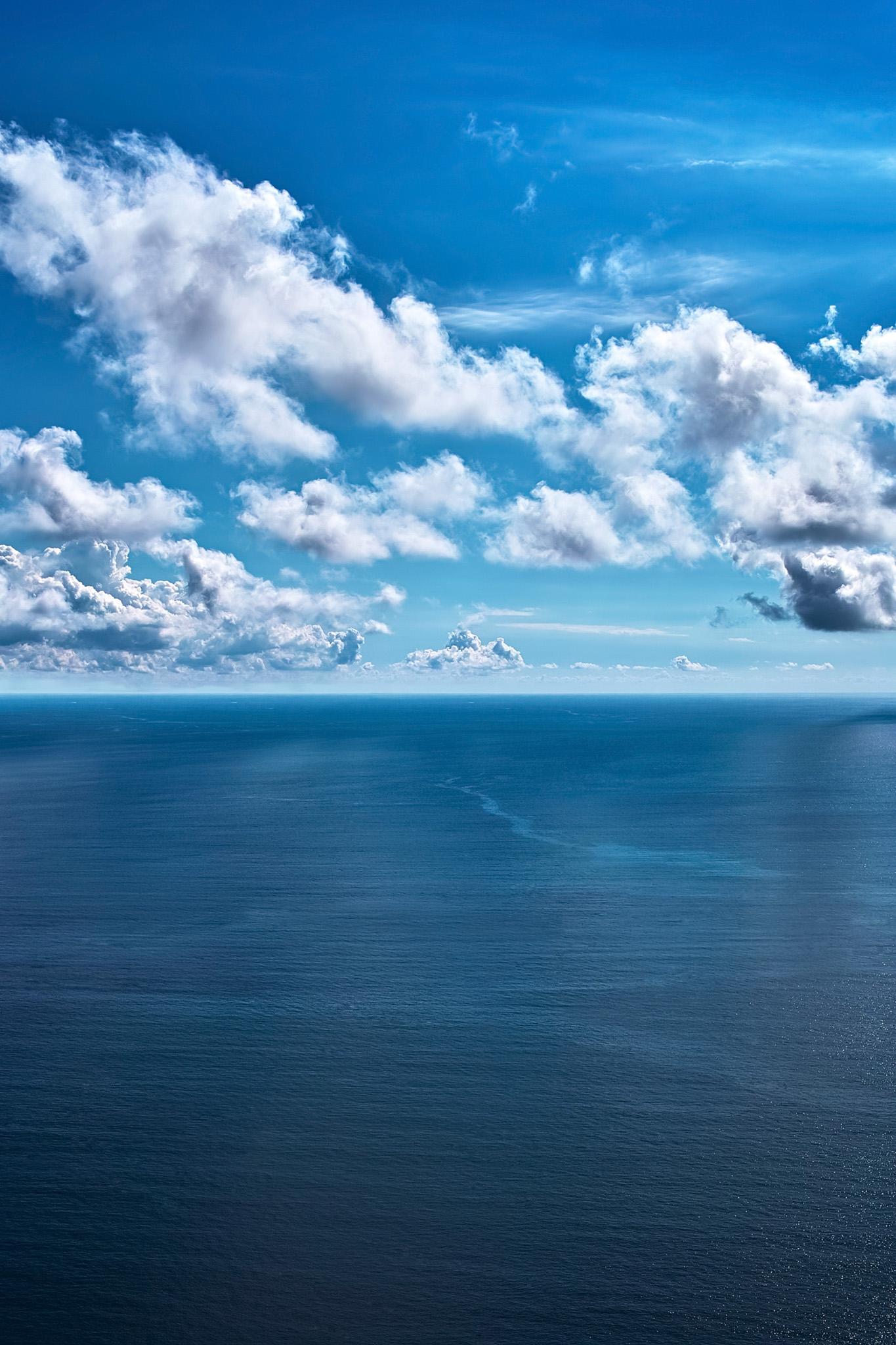 「紺碧の海面に映る空と雲」