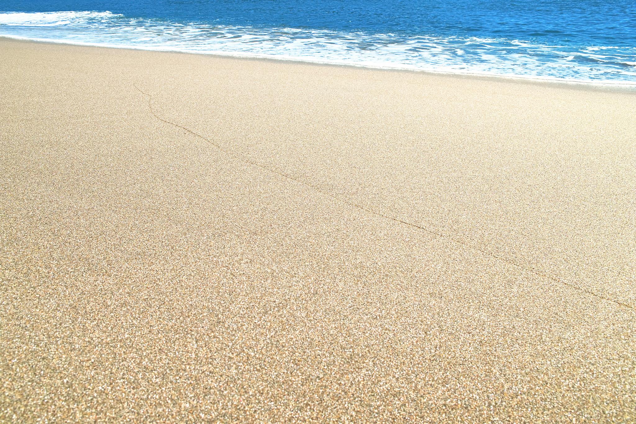 「静かな砂浜の波打際」