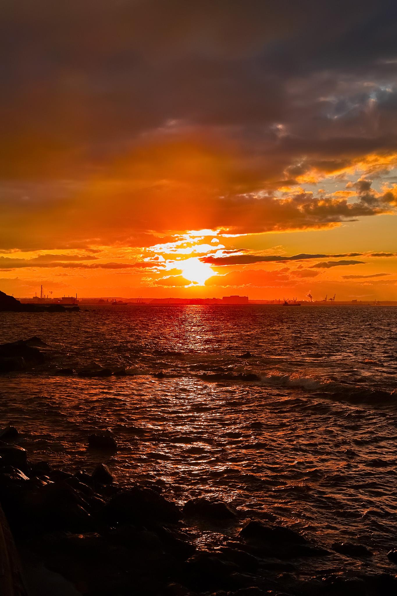 「夕日が沈む臨海の町」