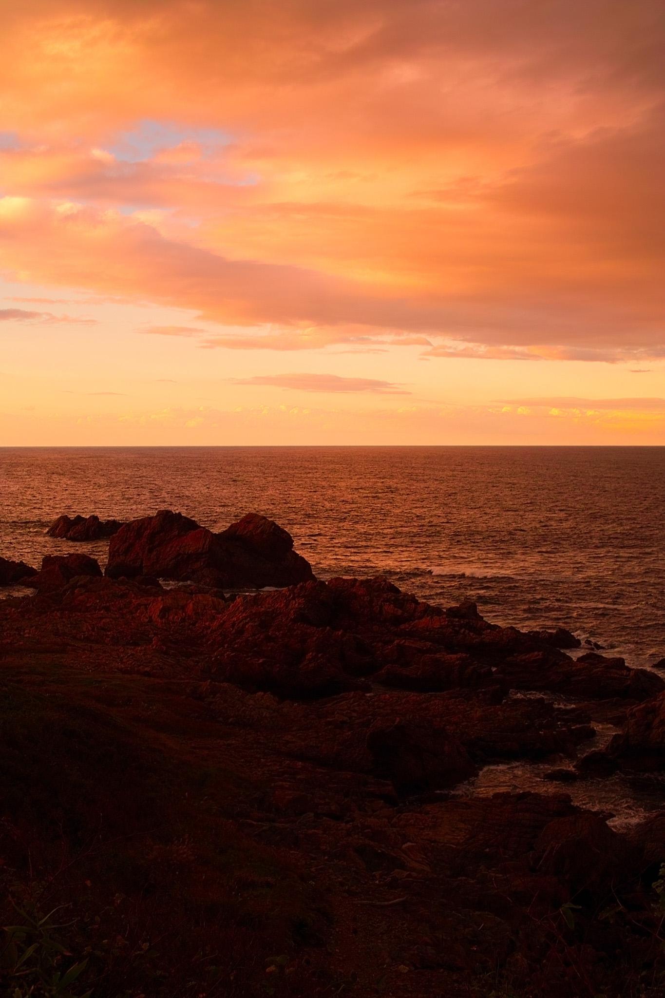 「夕焼けの岩の多い海岸」