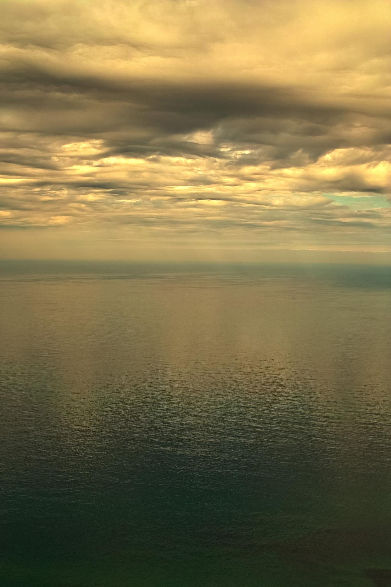 「黄金色の雲を写す穏やかな海」