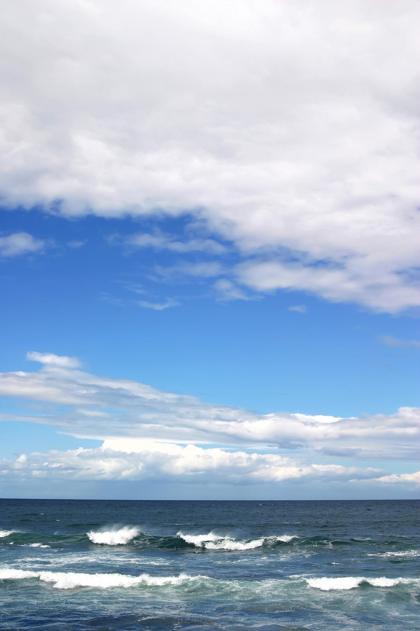 「夏の青空と波立つ海」