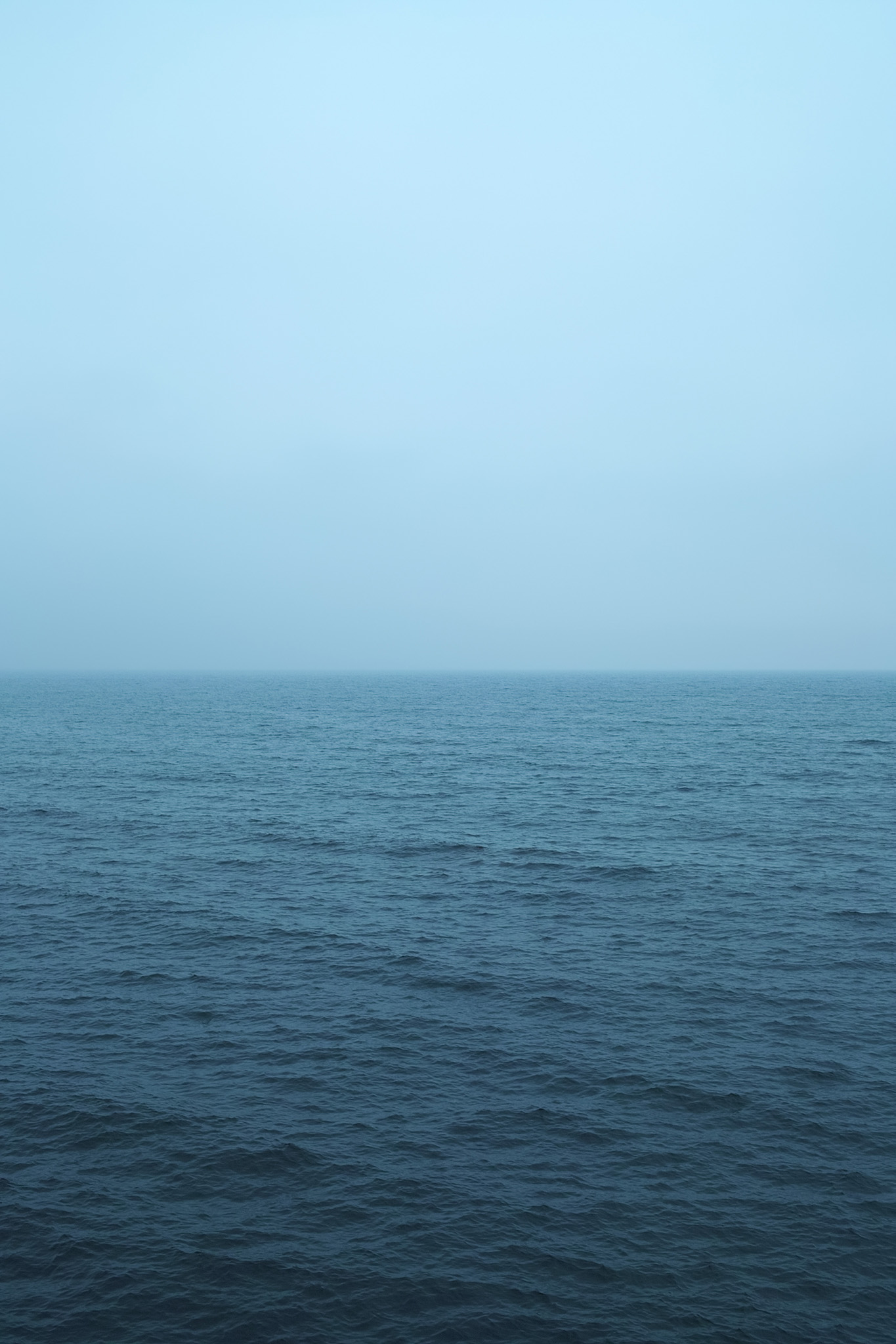 「薄曇りの空と暗い海」