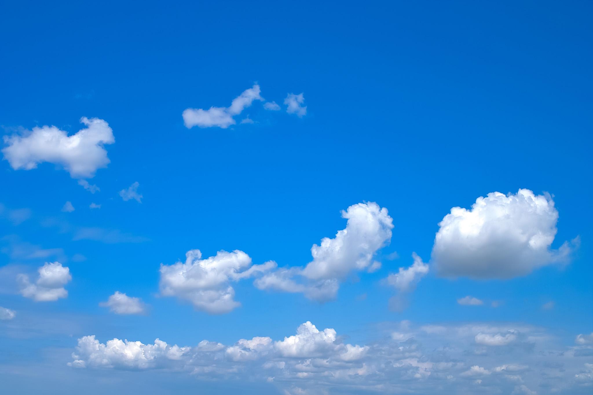 「ポツポツと雲が流れる青空」