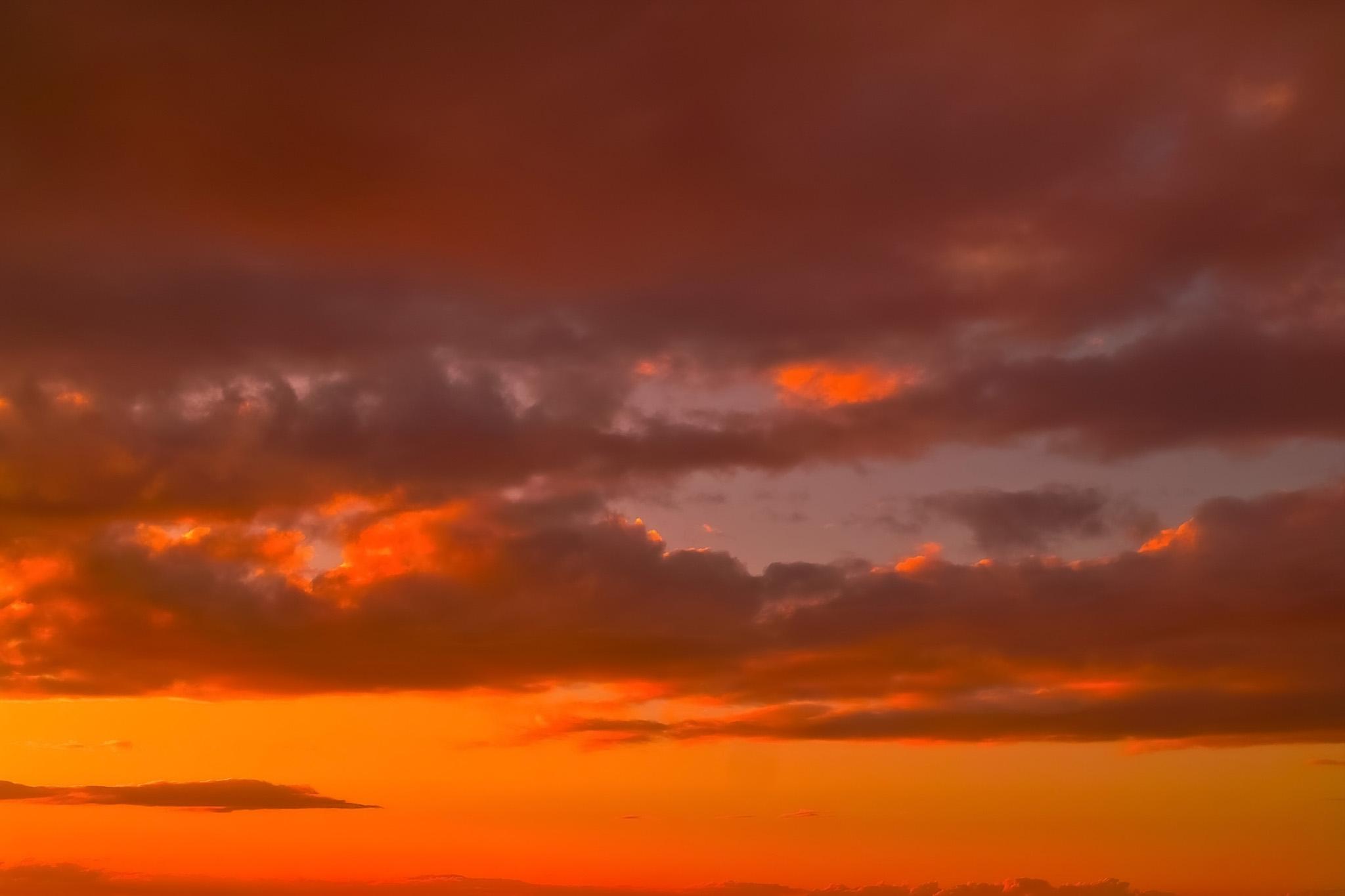 「夕焼けの空を温かい陽が照らす」