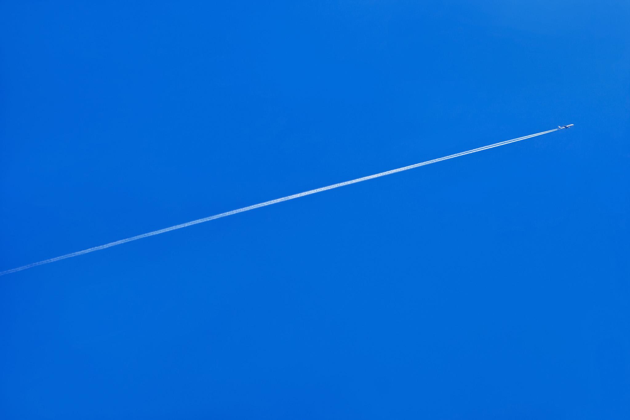 「青空に一直線を描く飛行機雲」