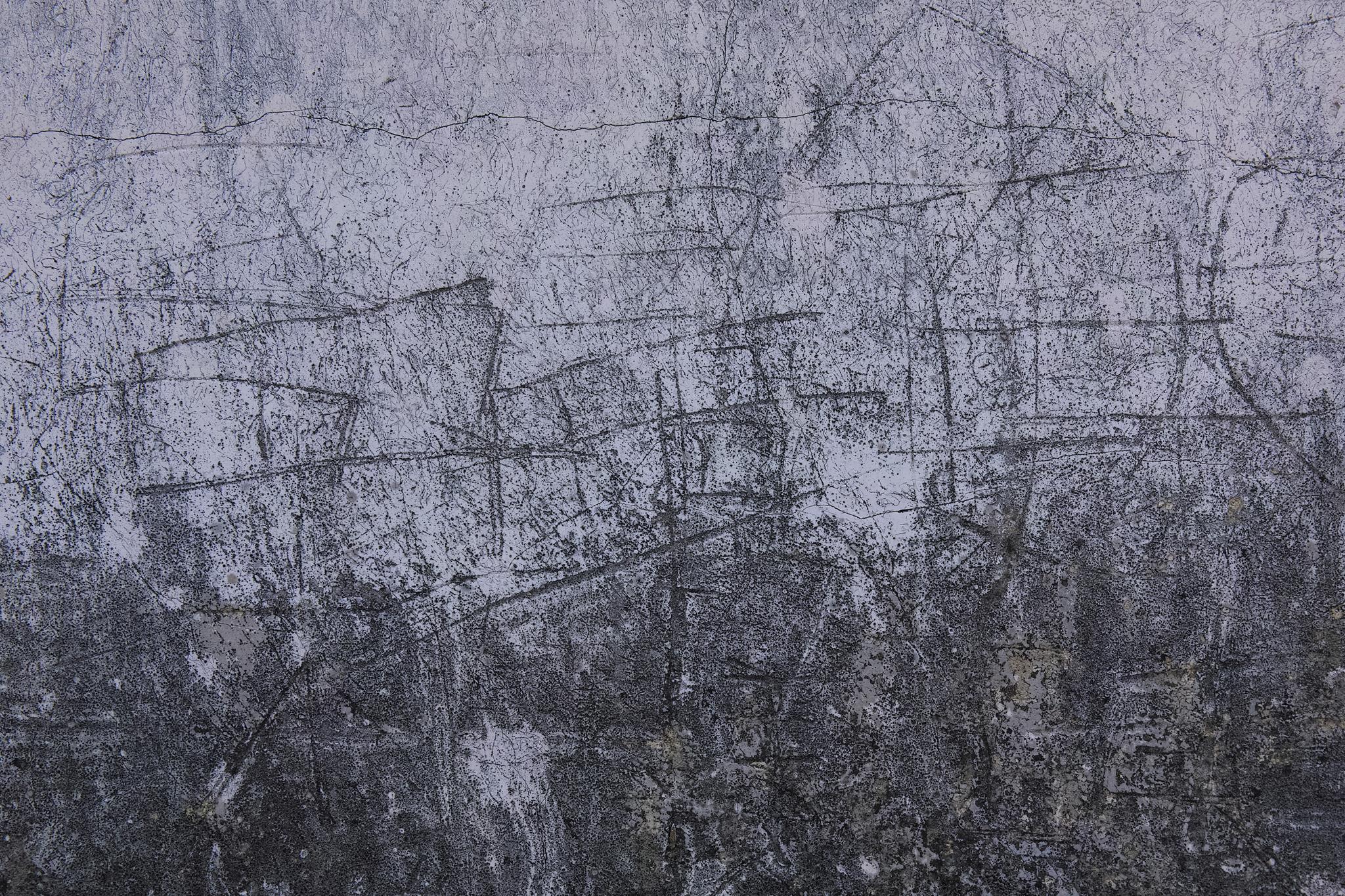 傷とヒビが入ったモルタルの壁