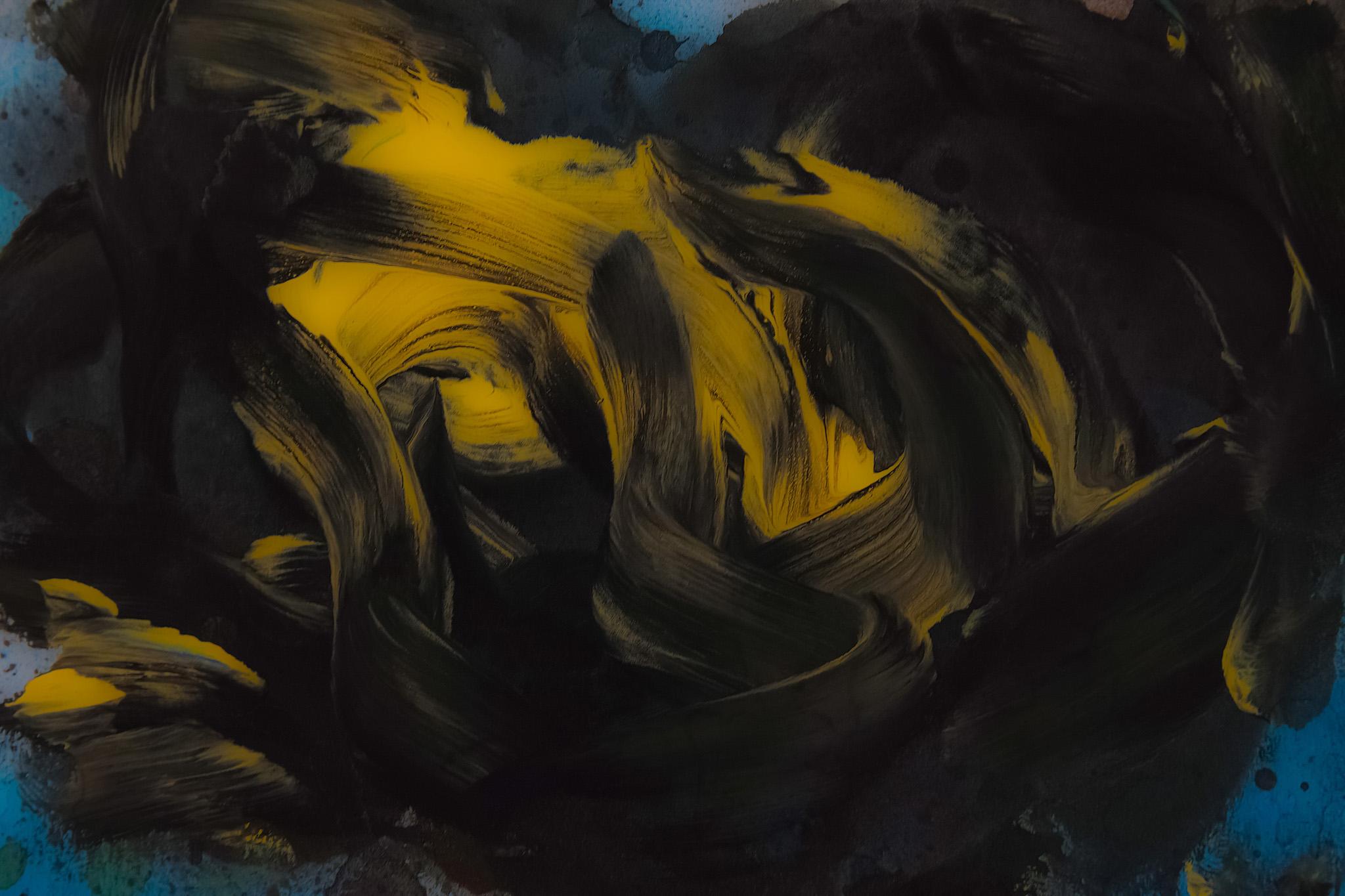 「混ざり合う黒色と黄色の絵具」