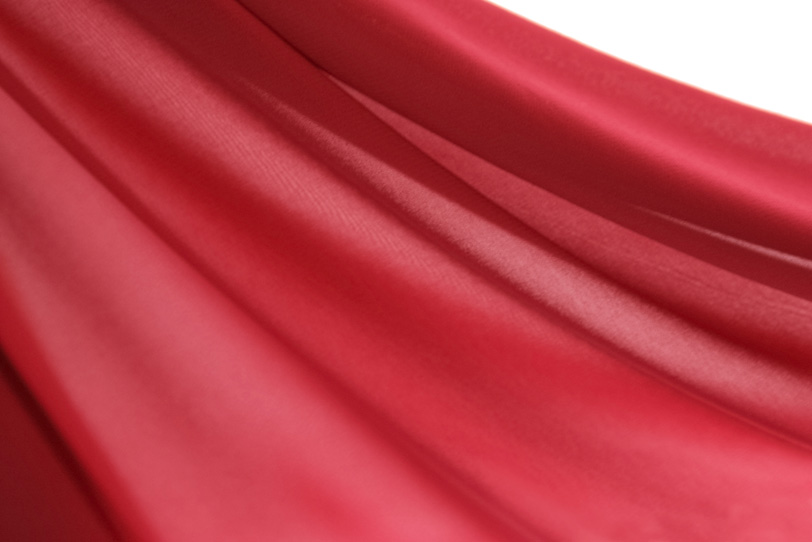 波打つ様なシワがある赤の布地の写真画像