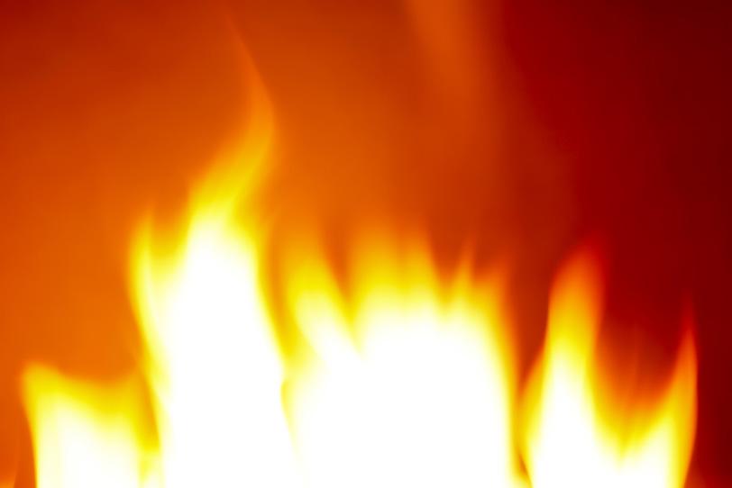 周りを赤く照らす火の写真画像