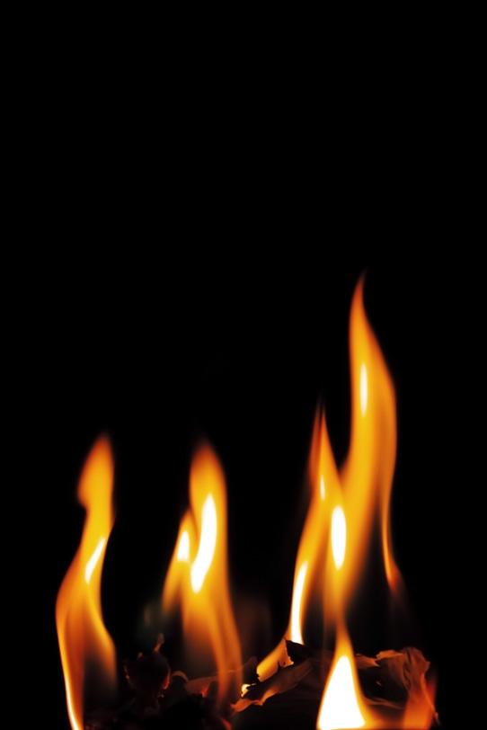黒い背景に4本の火柱の写真画像