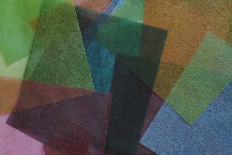 様々な色彩の薄い和紙を重ねた背景の写真画像