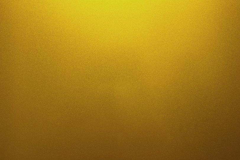 光を反射する金色の金属素材の写真画像