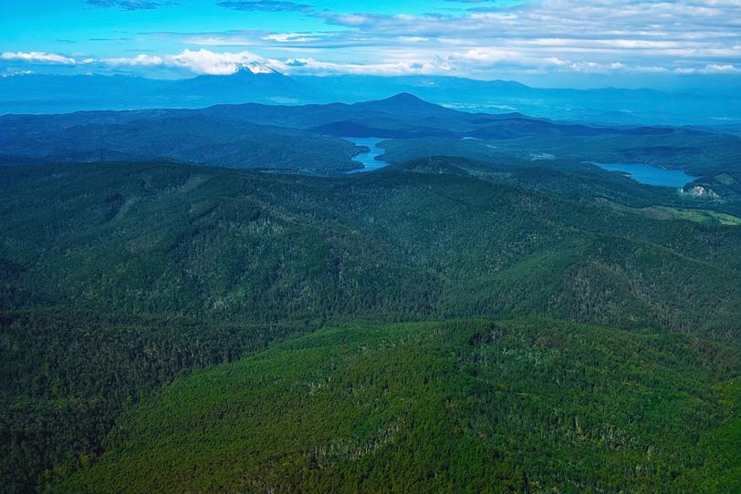 どこまでも続く山の向こうの幻想的な湖の写真画像