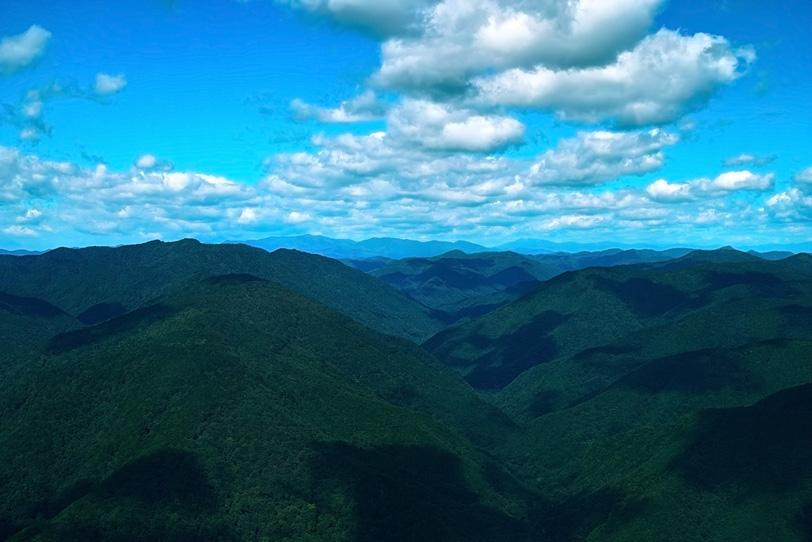 木々が生い茂る山脈に疎らに落ちる雲の影の写真画像