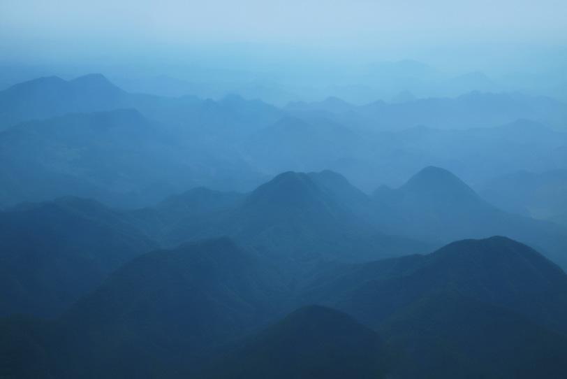 霧で霞んだ水墨画の様な山の風景の写真画像