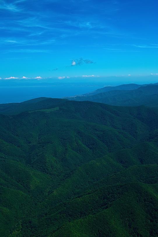 遠くに海が見える緑濃い山岳の写真画像