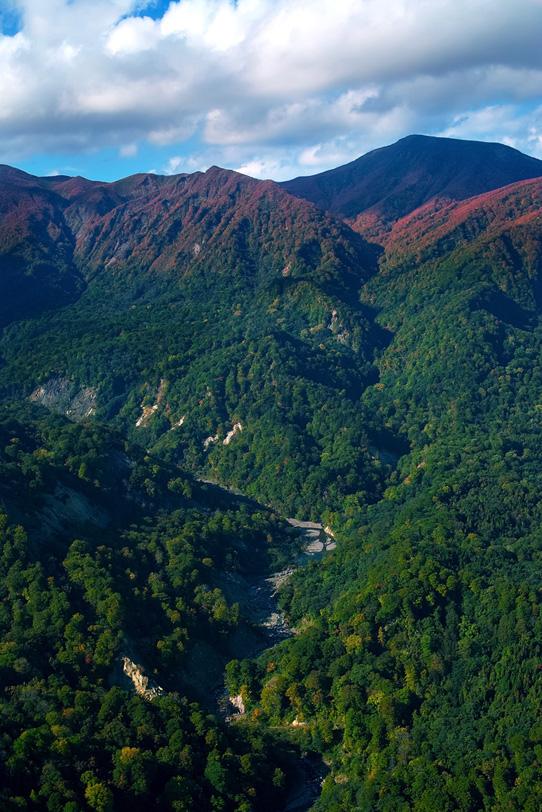 赤い山頂と緑の麓を流れる渓谷の写真画像