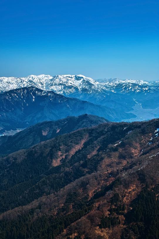 雪解けした山と雪残る山脈の写真画像