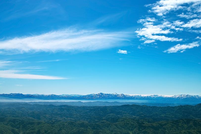 緑の山々の彼方にある残雪の山脈の写真画像