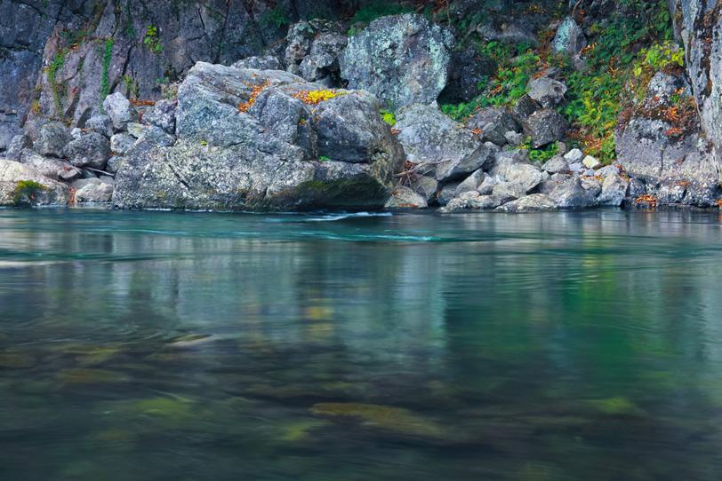 川底が見えるエメラルドグリーンの水と岩の写真画像