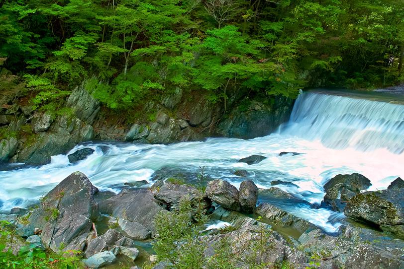 流れの激しい渓流にある堰堤の写真画像