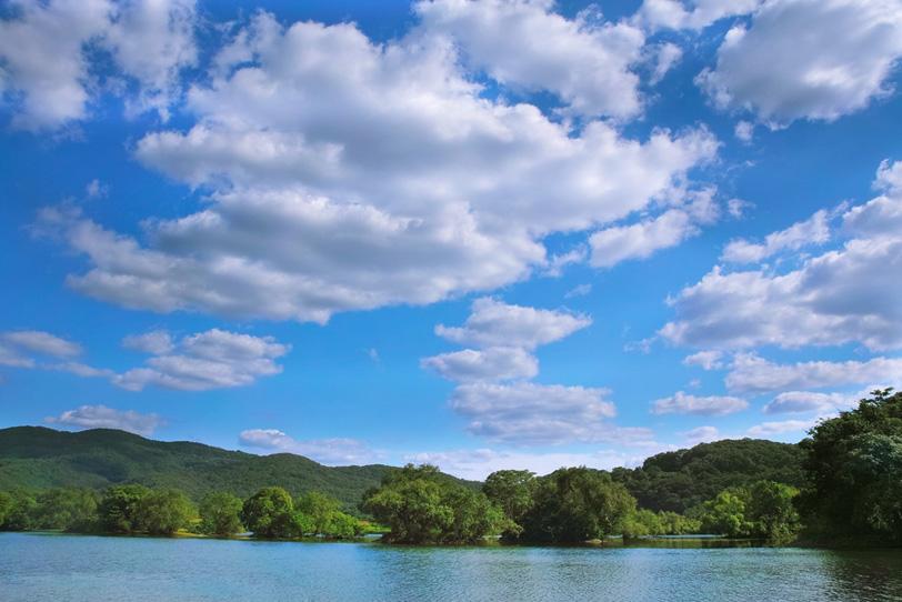 青空を映す穏やかな水面の川の写真画像