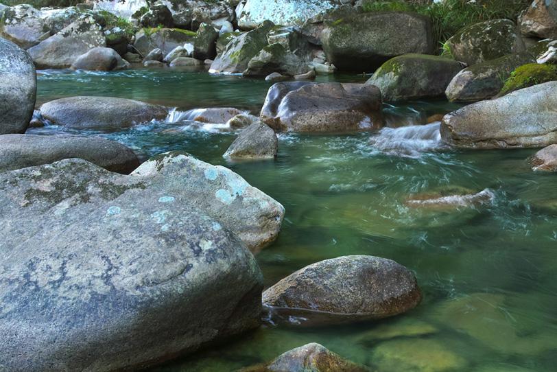 岩肌の質感が美しい川辺の写真画像