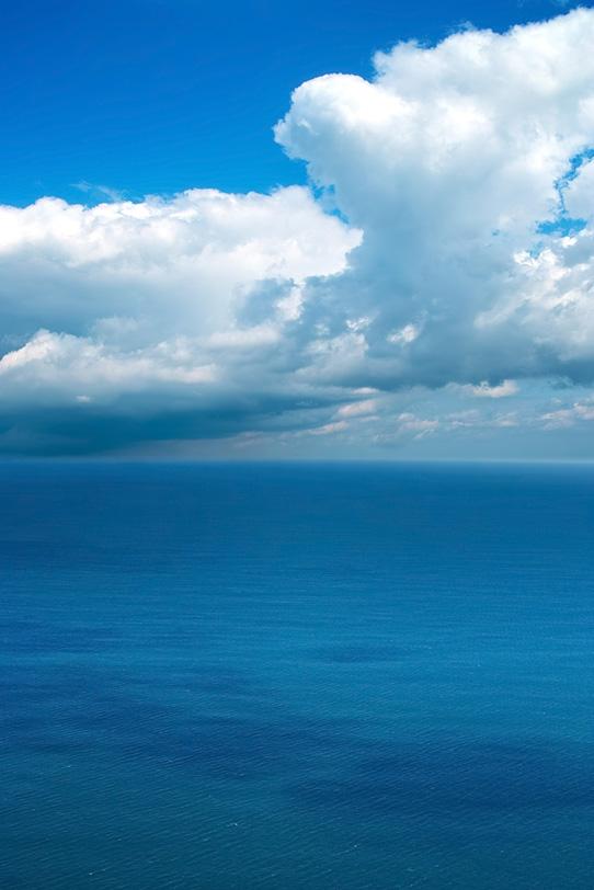 海と水平線の上の大きな雲の写真画像