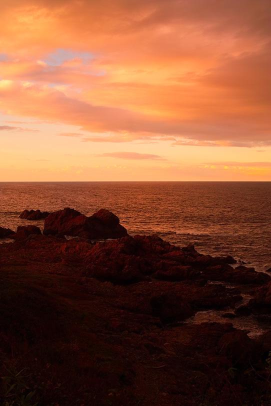 夕焼けの岩の多い海岸の写真画像