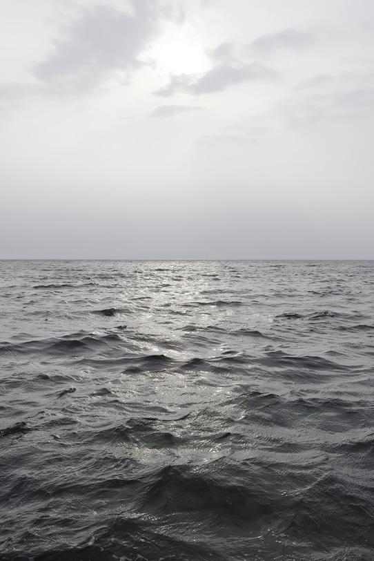 黒い海を照らす太陽の写真画像