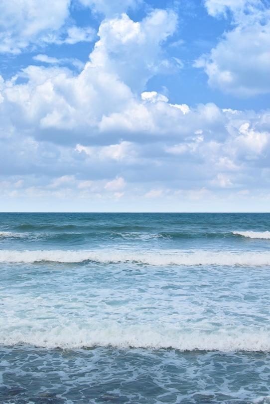 積乱雲と波寄せる夏のビーチの写真画像