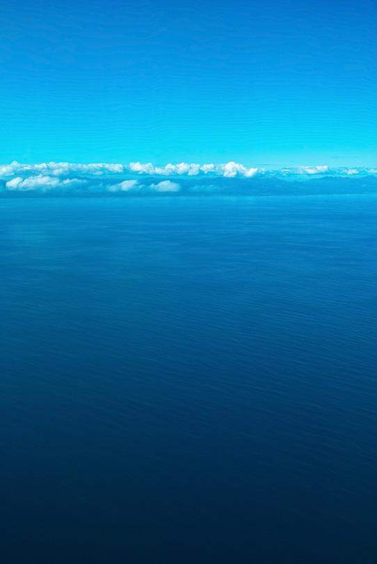 広大な海の向こうの陸地の写真画像