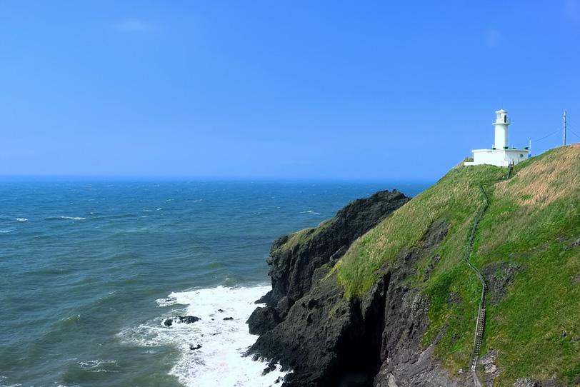 水平線と岬の灯台の写真画像