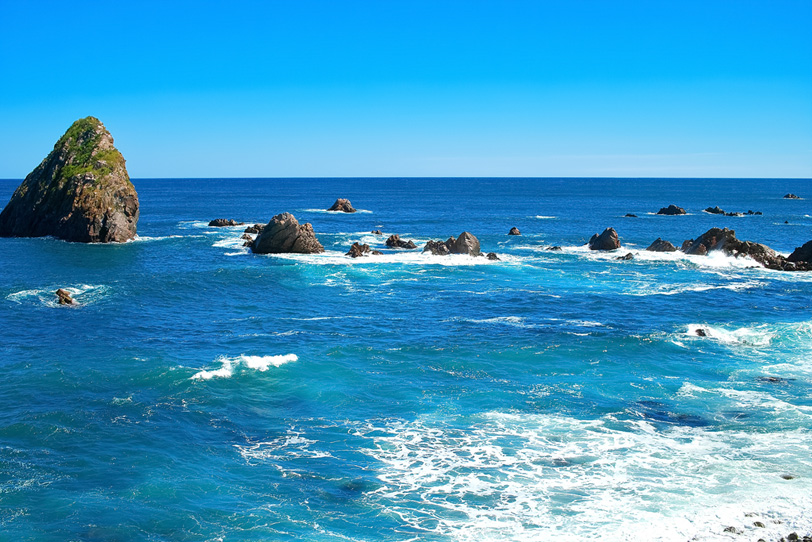 沖に見える大きな岩の写真画像