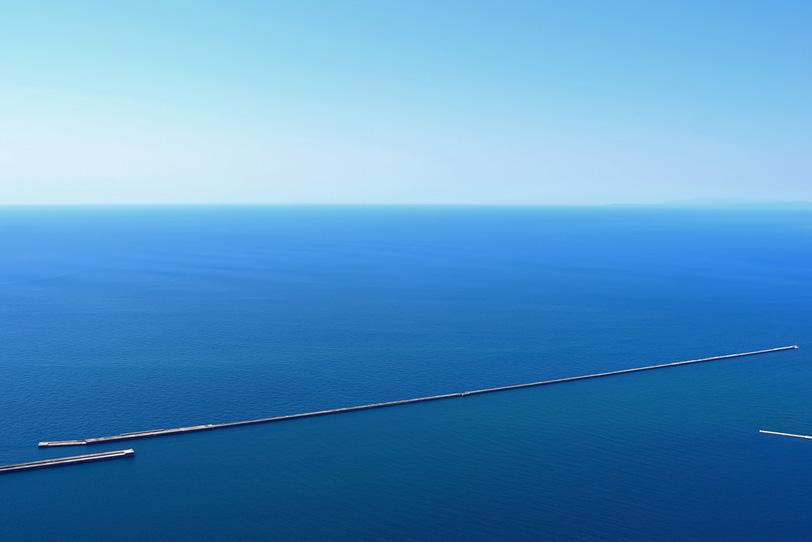 海に跨る長い防波堤の写真画像