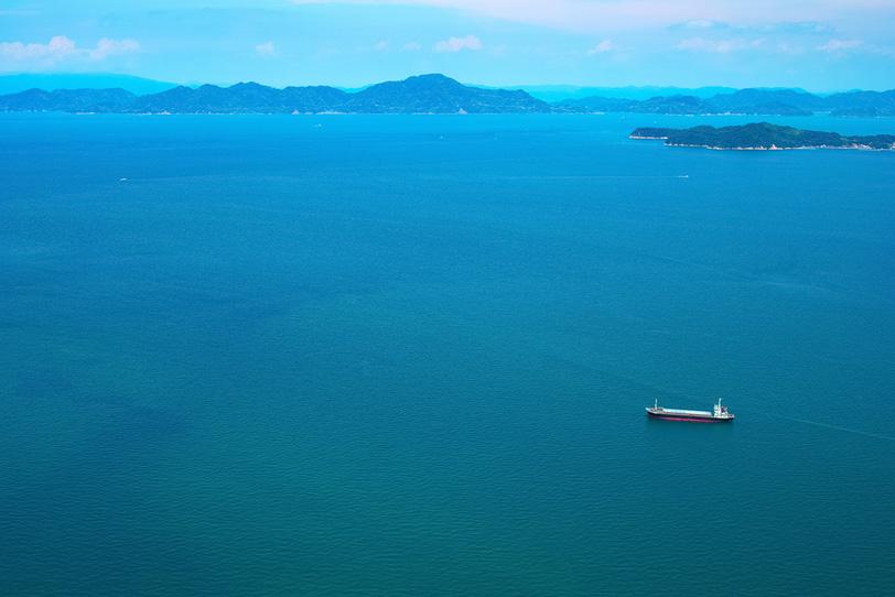 海に浮かぶ島と大きな船の写真画像