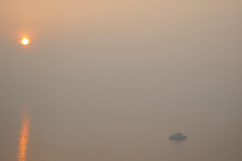 朝焼けの海に浮かぶ船の写真画像