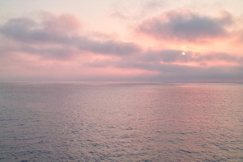 薄紅に染まる朝焼けの海の写真画像