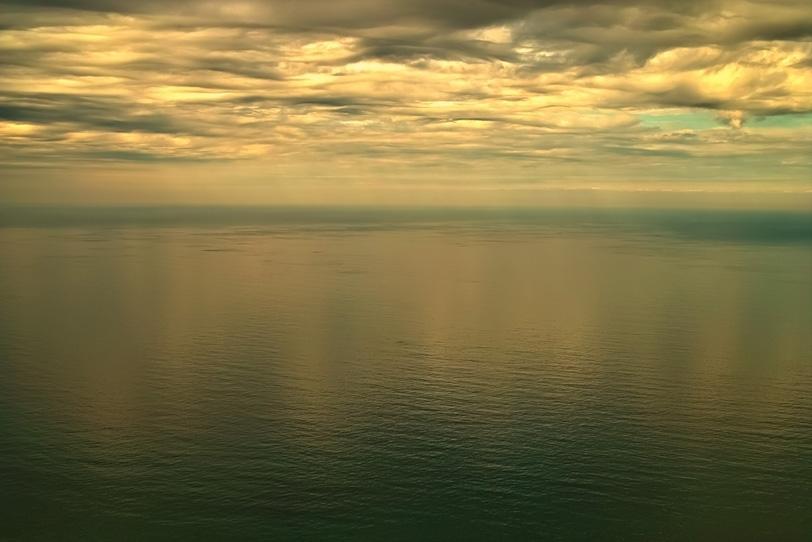 黄金色の空を反射する海の写真画像