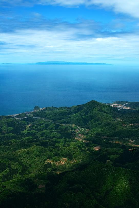 山の向こうに見える海の写真画像