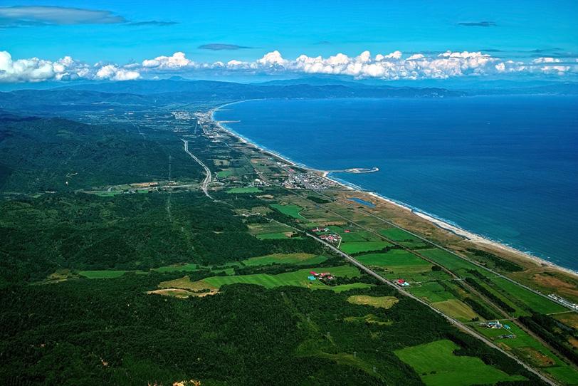 遠くに続く海岸と周辺の町の写真画像